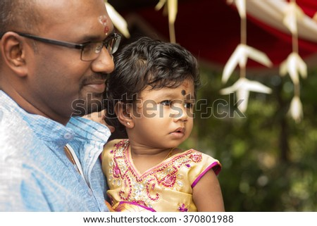 Candid shoot of Indian father and daughter in blessing ceremony. Traditional India family outdoor portrait.