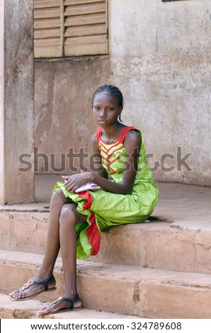 Candid shot of African Black Teenage Girl Sitting School Symbol. Candid photograph of beautiful African black teenage girl outside her classroom. - stock photo