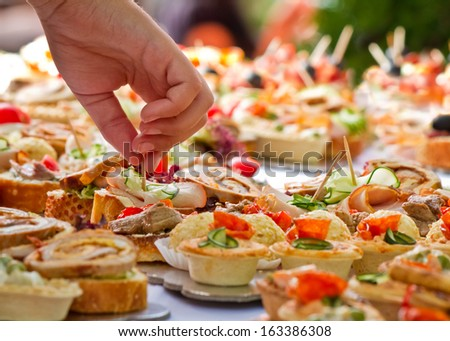Candid shot of human taking canape party catering. Outdoor shot. - stock photo