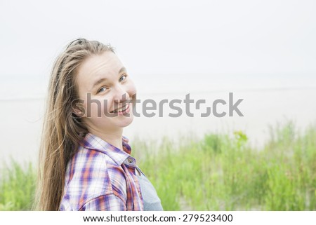 Candid shot of smiling young blond woman on empty beach in plaid shirt with copy space - stock photo
