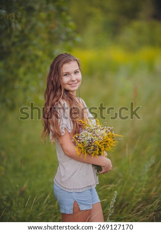 Candid skipping carefree adorable woman in field with flowers at summer sunset. - stock photo