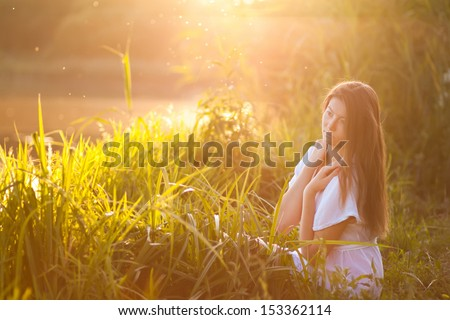 Candid skipping carefree adorable woman lay in field at summer sunset - stock photo