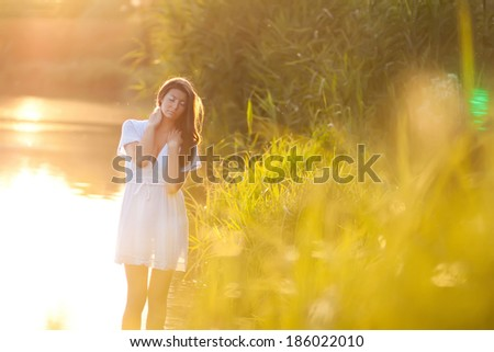 Candid skipping carefree adorable woman with long hair standing in water at summer sunset. - stock photo