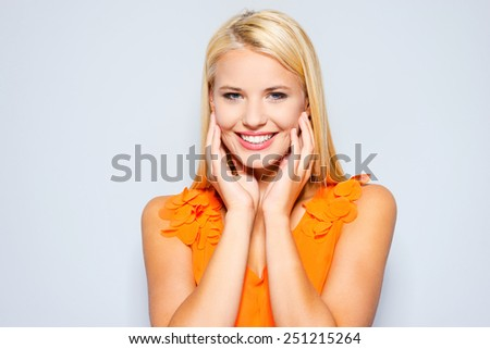 Candid smile. Beautiful young blond hair women holding hands on her cheeks and looking at camera while standing against grey background  - stock photo