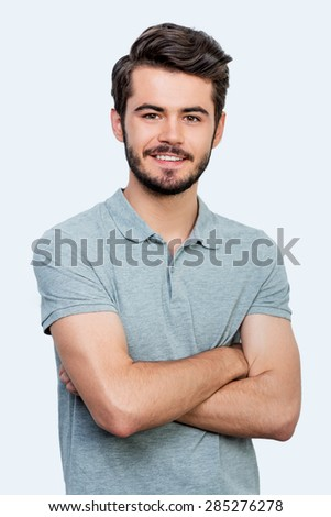 Candid smile. Handsome young man keeping arms crossed and looking at camera while standing against white background - stock photo