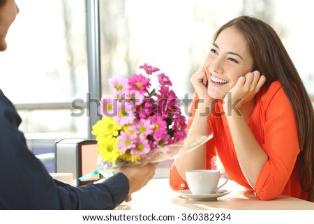 Candid woman dating in a coffee shop and looking her boyfriend who gives her a bunch of flowers - stock photo