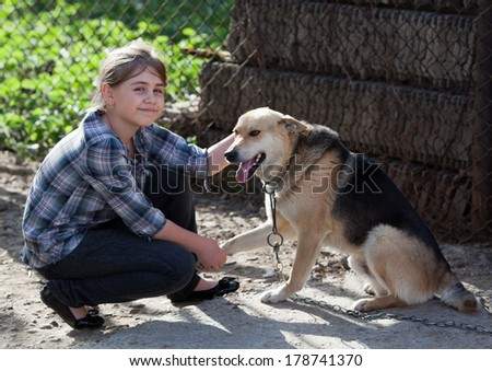 Candid young girl holding stray dog. Positive feeling - stock photo