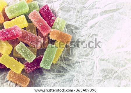 Candied fruit jelly sweets on paper - vintage look - stock photo
