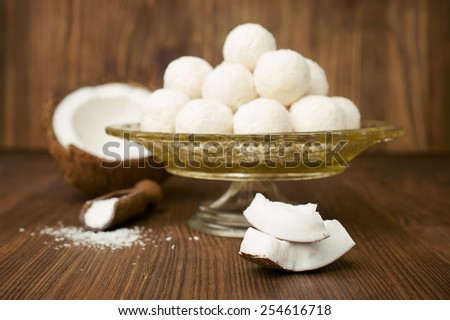 candies in coconut flakes and fresh coconut on a wooden background - stock photo