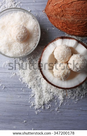Candies in coconut flakes and fresh coconut on color wooden background - stock photo