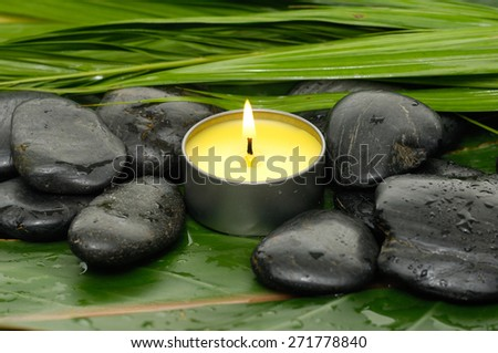 Candle and black stones on wet banana leaf - stock photo