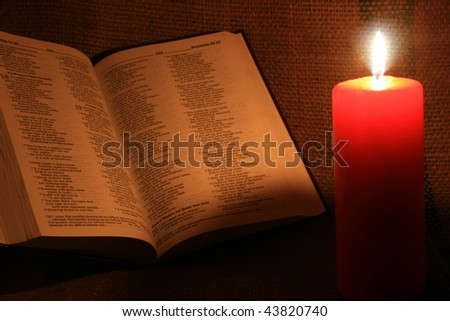 candle and book in darkness
