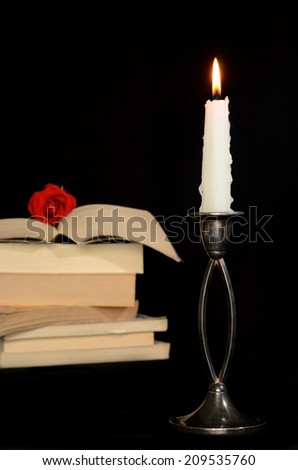 Candle and books on black background