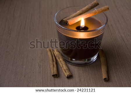 Candle and Cinnamon against the Wooden Surface