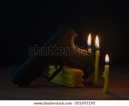 candle and gun on black background, 3 candle, wooden table,