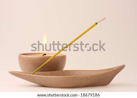 Candle and incense stick in pastel shades - stock photo