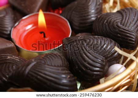 candle at center of home made chocolates - retro style - stock photo
