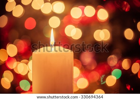 Candle burning in front of Christmas tree lights with vintage filtering