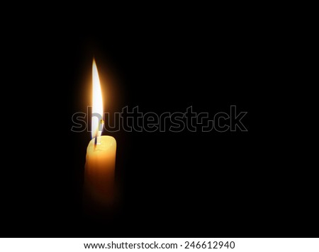 candle burning on a dark background - stock photo