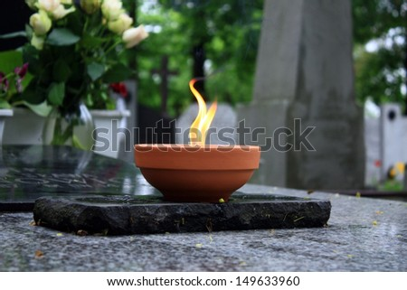Candle burning on cemetery on tombstone - stock photo