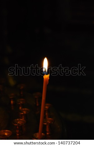 candle burns near icons in orthodox church - stock photo