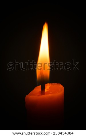Candle flame closeup isolated on black. - stock photo