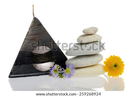 Candle, flowers and stones stacked isolated with reflection - stock photo