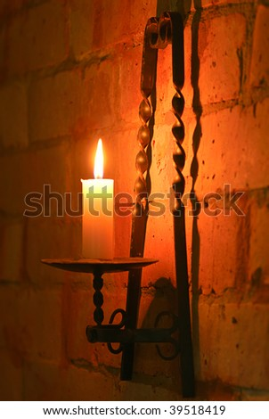 Candle in brass holder lighting wall of brick - stock photo