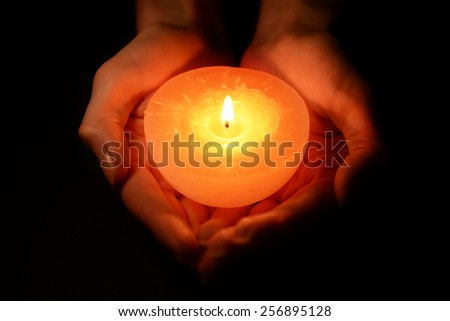 Candle in female hands on black background - stock photo
