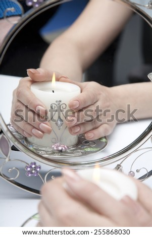 Candle in female hands. The reflection in the mirror - stock photo