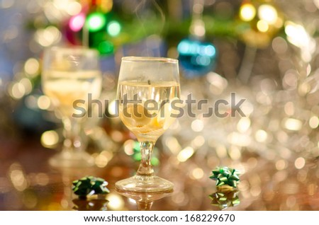 candle in form of wine glass with seashells in front of Christmas tree