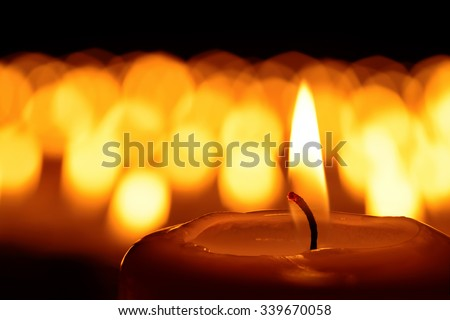 Candle in front of many defocused candleflames creating a spiritual atmosphere and in remembrance of loved ones - stock photo