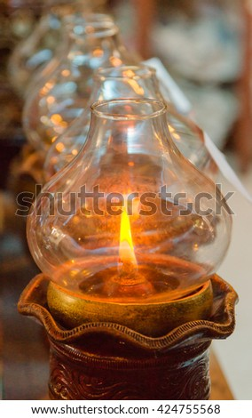 candle in glass lantern at the night. Buddha candle. Image has shallow depth of field. - stock photo
