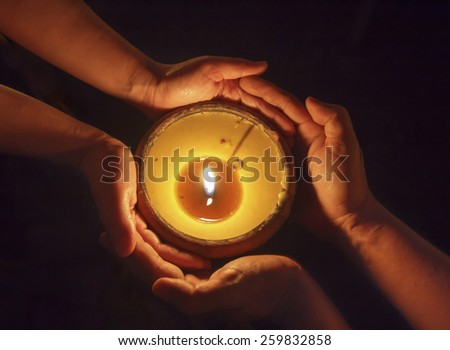 Candle in the hands together - stock photo
