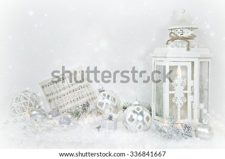 candle in white lantern with holiday ornaments in snow