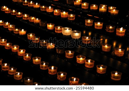 Candle lights arranged in rows, on the black background
