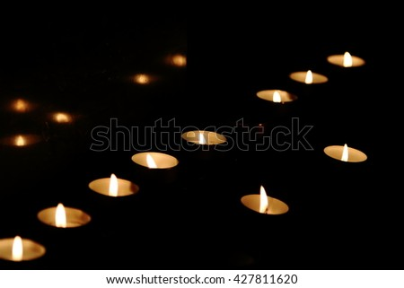 Candle lights in a church in the dark for prayers - stock photo