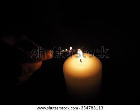 candle lit match on a black background