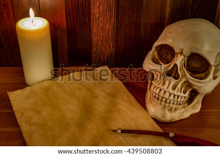 Candle lit scene of a skull, aged paper with a pentagram wax seal on it and a red feather fountain pen, Halloween