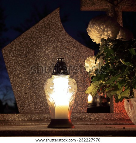 Candle on a grave at night