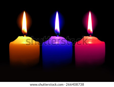 Candle  Orange Pink Blue color on over dark background  - stock photo