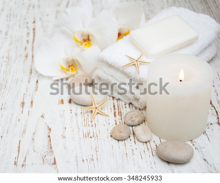 Candle, orchids and towels on a wooden background