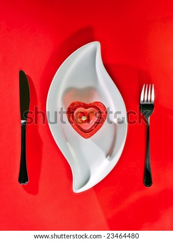 Candle shaped heart on white plate and red background