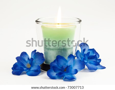 Candle with blue flowers - stock photo