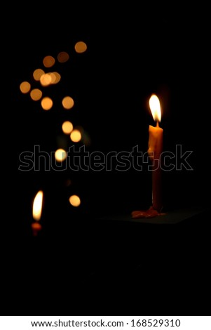 Candle with fire isolated on black background - stock photo