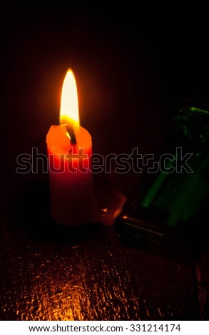 candle with green lighter on wood background by dark tone. - stock photo