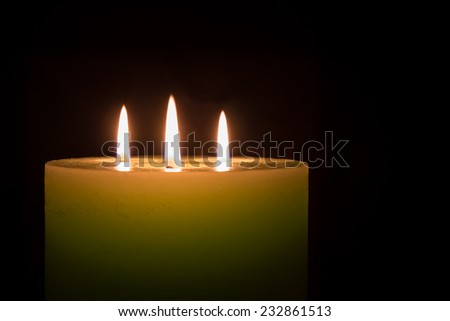 Candle with three flames on black background with copy space
