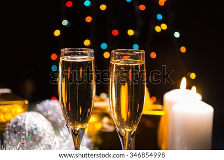 Candlelight champagne Christmas background with two glasses of champagne lit by two burning candles over a background bokeh os colorful sparkling party lights