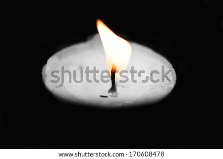 candlelight,  selected color on the flame,  black and white macro shot isolated on black - stock photo