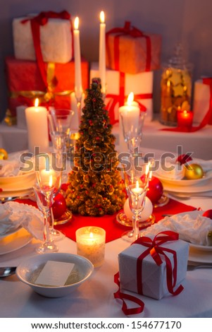 Candlelight, wafer and gifts on the Christmas table